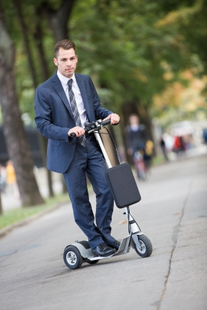 locomotion: Young businessman in a park riding a pedal-scooter