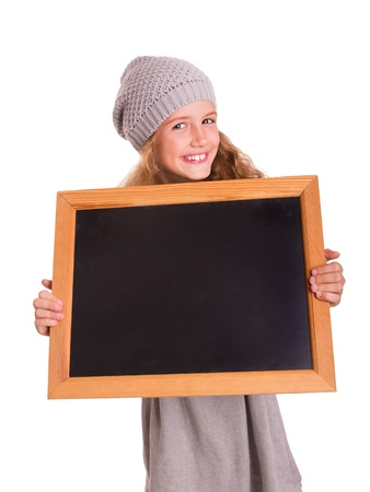 Young cute girl holds a small blackboard and is smiling into the camera photo