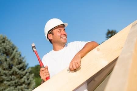 roofer: Friendly artisan working hard to build the roof of a new house Stock Photo
