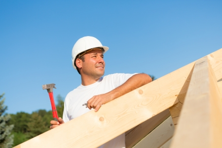 Young artisan working hard to build the roof of a new house