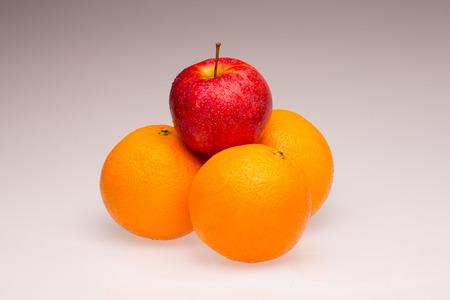 Sinaasappelen en een rode appel als een symbool en het concept voor differentiatie en concurrentie