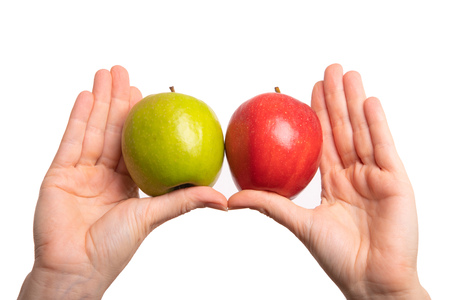 Compare and differentiate red and green apples. Colourful fruits isolated in front of white background.