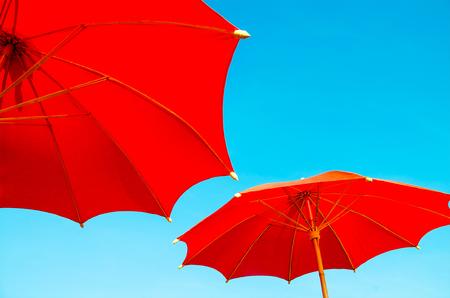 red beach umbrella with blue sky