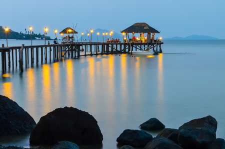 Wooden pathway with small hut over sea with lights at evening