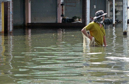 LAMLUKKA (PATHUMTHANI), THAILAND � CIRCA NOVEMBER 2011 � An unidentified man fishes with a net in the floodwater circa November 2011 in Lamlukka. The entire province has been flooded as a result of an exceptional and unprecedented rainy season.