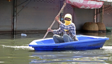 obliteration: LAMLUKKA (PATHUMTHANI), THAILAND – CIRCA NOVEMBER 2011 – An unidentified man rows his boat through a flooded road circa November 2011 in Lamlukka. The entire province has been flooded as a result of an exceptional and unprecedented rainy season.