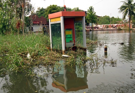 phonebox: LAMLUKKA (PATHUMTHANI), THAILAND � CIRCA NOVEMBER 2011 � A flooded phonebox stands solitary in the middle of a desolate area circa November 2011 in Lamlukka. The entire province has been flooded as a result of an exceptional and unprecedented rainy season