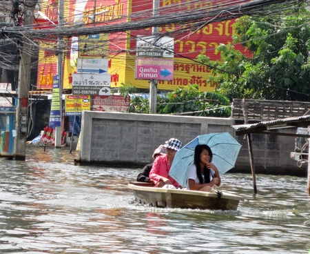 obliteration: LAMLUKKA (PATHUMTHANI), THAILAND � CIRCA NOVEMBER 2011 � Three unidentified people sail through a flooded road circa November 2011 in Lamlukka. The entire province has been flooded as a result of an exceptional and unprecedented rainy season.
