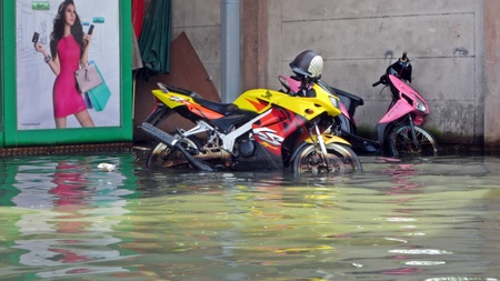 obliteration: LAMLUKKA (PATHUMTHANI), THAILAND – CIRCA NOVEMBER 2011 – Two neglected motorbikes stand in the middle of the floodwater circa November 2011 in Lamlukka. The entire province has been flooded as a result of an exceptional and unprecedented rainy season.
