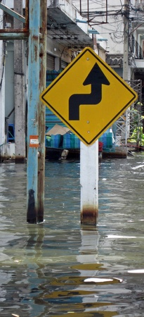 obliteration: LAMLUKKA (PATHUMTHANI), THAILAND – CIRCA NOVEMBER 2011 – A double curve road sign stands in the middle of the floodwater circa November 2011 in Lamlukka. The entire province has been flooded as a result of an exceptional and unprecedented rainy season.  Editorial