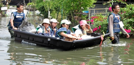 LAMLUKKA (PATHUMTHANI), THAILAND � CIRCA NOVEMBER 2011 � An unidentified rescue team pushes a boat that transports a group of unidentified people through a flooded road circa November 2011 in Lamlukka.