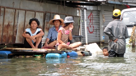 obliteration: LAMLUKKA (PATHUMTHANI), THAILAND � CIRCA NOVEMBER 2011 � A group of unidentified people sits on an improvised raft while a boy swims in the floodwater circa November 2011 in Lamlukka.