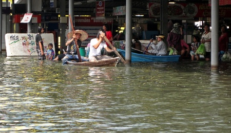 obliteration: LAMLUKKA (PATHUMTHANI), THAILAND � CIRCA NOVEMBER 2011 � A group of unidentified people in an inundated fresh market circa November 2011 in Lamlukka. The entire province has been flooded as a result of an exceptional and unprecedented rainy season.  Editorial