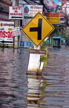"""LAMLUKKA (PATHUMTHANI), THAILAND – CIRCA NOVEMBER 2011 – A """"T intersection� road sign stands in the middle of the floodwater circa November 2011 in Lamlukka. The entire province has been flooded as a result of an exceptional and unprecedented rainy season"""