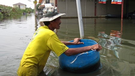 obliteration: LAMLUKKA (PATHUMTHANI), THAILAND – CIRCA NOVEMBER 2011 – A man with a hat pushes a barrel through the flood waters circa November 2011 in Lamlukka. The entire province has been flooded as a result of an exceptional and unprecedented rainy season.