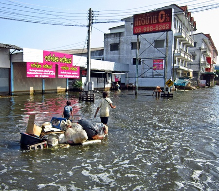 rainfall: LAMLUKKA (PATHUMTHANI), THAILAND � CIRCA NOVEMBER 2011 � Two unidentified people pull an improvised raft with some goods through a flooded road circa November 2011 in Lamlukka. The entire province has been flooded as a result of exceptional rainfall.