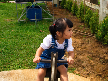 totter: 2-year-old Asian-Caucasian girl plays on a seesaw