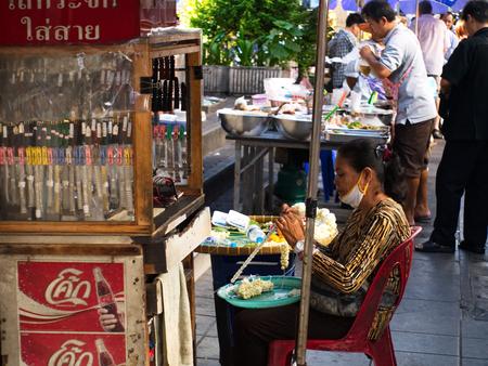silom: Bangkok, THAILAND - CIRCA JUNE 2015 - An unidentified lady sells flowers on a street side market circa June 2015 in Silom Road, Bangkok, Thailand.