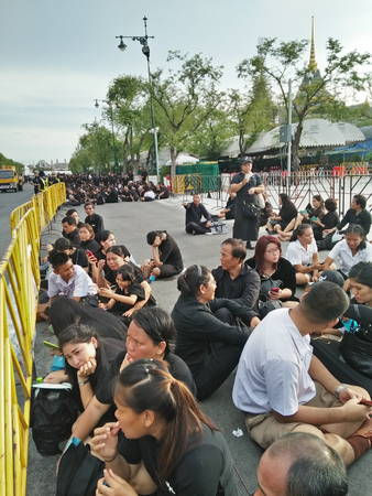 Unidentified mourners sitting on the floor waiting under the sun outside the Grand Palace in Bangkok (Thailand)  to pay respect to HM the King Rama IX on 09092017 Editorial