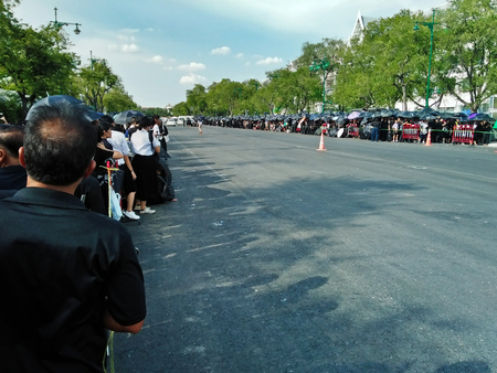 Unidentified mourners standing in a long line under the sun outside the Grand Palace in Bangkok (Thailand)  to pay respect to HM the King Rama IX on 09092017