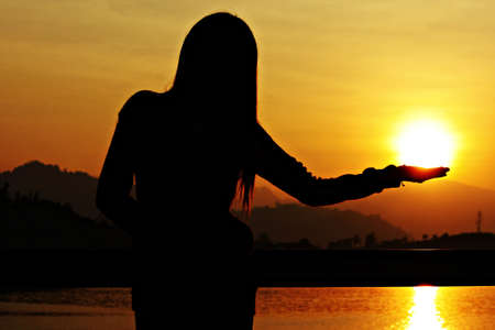 beautiful young woman standing on bridge, watching sunset, holding sun in hand photo