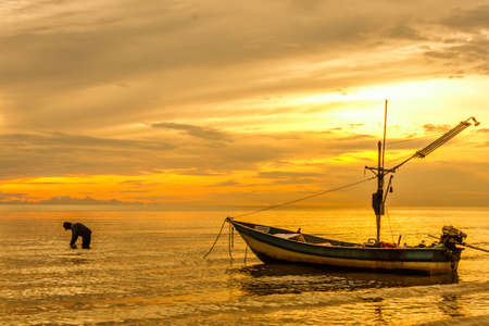 Golden sky during sunset at the beach with fishermen photo