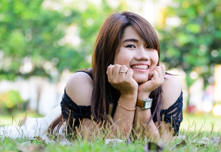 Beautiful Girl lying on the Field.Green Grass. Happy and Smiling photo