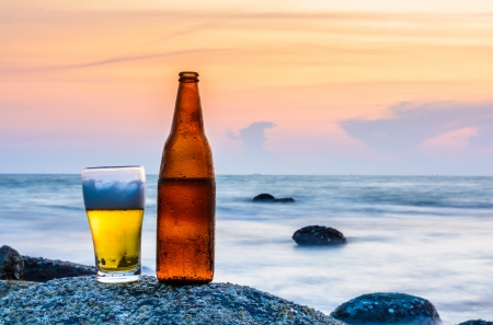 Glass of beer and a bottle on the rock at sea photo