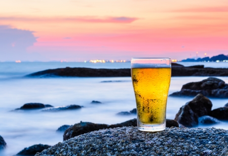 Cup of beer standing on the rock at sea, Thailand