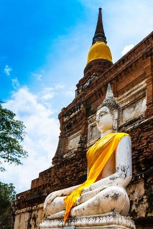 far eastern: Ancient Buddha statues against blue sky at Wat Yai Chai Mongkol in Ayutthaya, Thailand