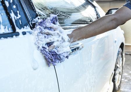 lavar: asimiento de la mano una esponja sobre el coche para el lavado Foto de archivo