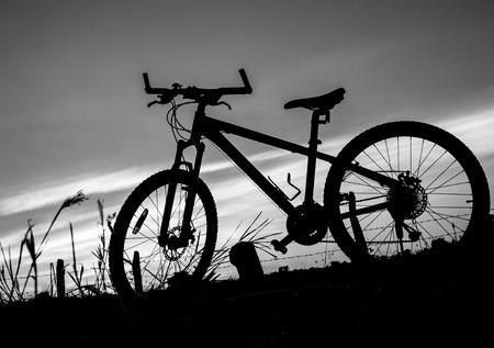fondo blanco y negro: Negro bicicleta blanca en una puesta de sol