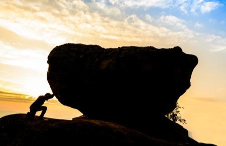 upward struggle: Hard work.The person rolls the rock on mountain. Stock Photo