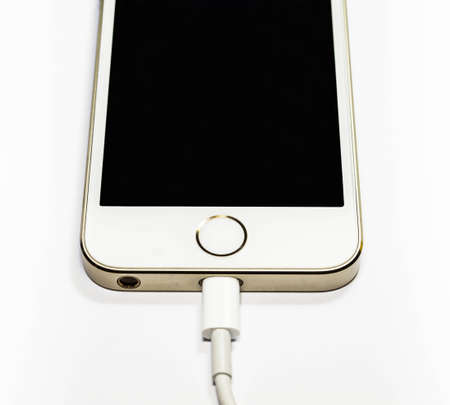 Modern mobile phone on charge. On a white background Stock Photo