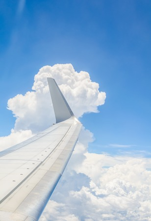 clouds sky: Wing of an airplane flying above the clouds Stock Photo