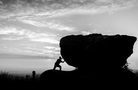 upward struggle: Hard work.The person rolls the rock on mountain Stock Photo