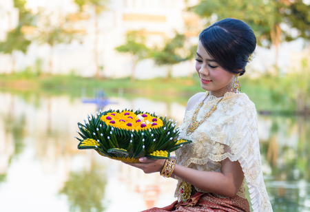 Thai women welcome with traditional Thai suit with Krathong, Loy Krathong fastival of Thailand Stock Photo