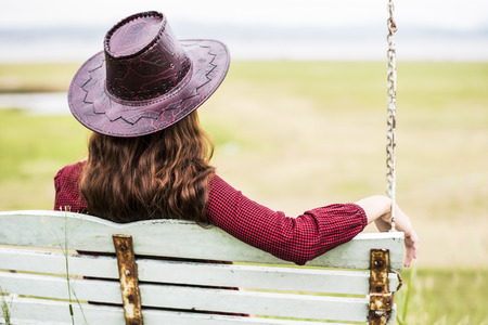 mujer mirando el horizonte: Single woman alone swinging on the beach Foto de archivo