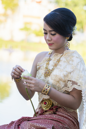 Beautiful Thai girl in Thai traditional costume trying to  roll lup lotus