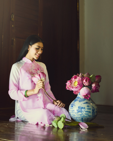 Portrait of Vietnam girls with Ao Dai preparing flower, lotus in jug.