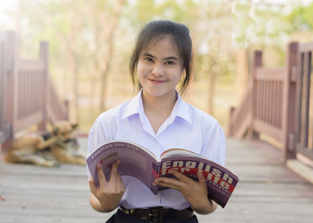 A student is reading a English book for test at garden Stock Photo