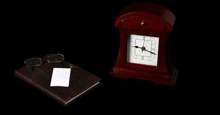 datebook: Clock and datebook with glasses lying near card Stock Photo