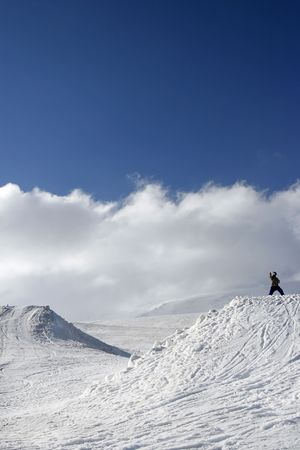 Snowboarder poses a ninja in mountains photo