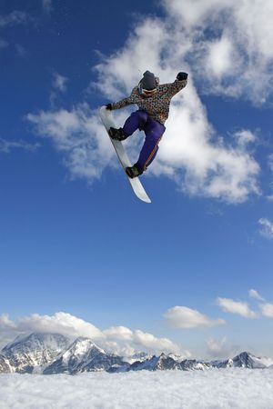 Modern snowboarder jumping very high at springboard photo