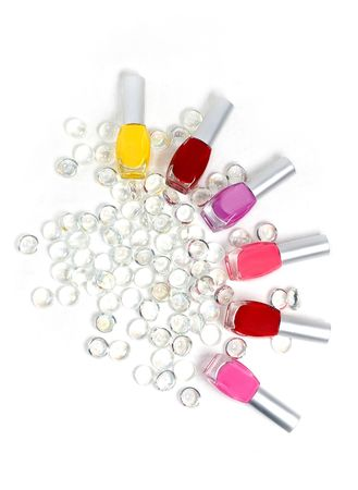 Colorfull nail polishes laying in jewels photo