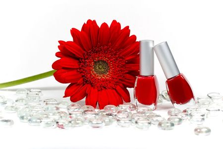 Red flower, two nail polishes and jewels photo