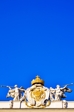 crest with two white marble angel sculptures with trumpets against blue sky photo