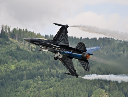 airpower: f-16 fighter jet doing aerobatics at an airshow Editorial
