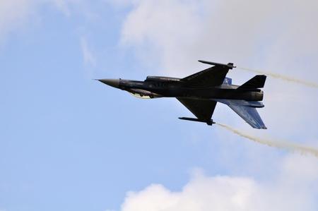 avion de chasse: jet chasseur F-16 fait la voltige à un meeting aérien