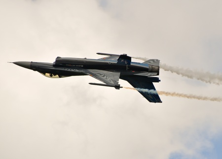 f-16 fighter jet doing aerobatics at an airshow Editorial